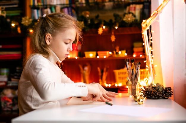Adorável menina está escrevendo uma carta para santa klaus sentado em cima da mesa