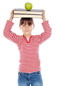 Adorável menina estudando com livros e apple na cabeça
