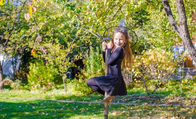 Adorável menina fantasiada de bruxa halloween se divertindo na vassoura