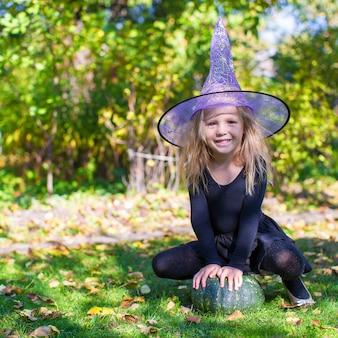 Adorável menina fantasiada de bruxa lança um feitiço no halloween