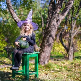 Adorável menina fantasiada de bruxa no dia das bruxas