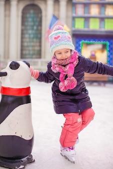 Adorável menina feliz desfrutando de patinar na pista de gelo