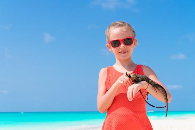 Adorável menina feliz detém um lagarto tropical selvagem na praia tropical branca