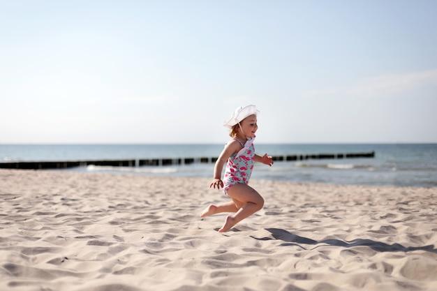 Adorável menina feliz e sorridente de férias na praia, pulando na praia