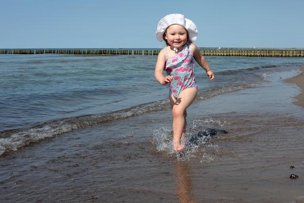 Adorável menina feliz e sorridente em férias na praia, correndo ao longo da costa