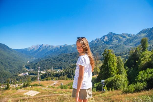 Adorável menina feliz nas montanhas no fundo de uma bela paisagem