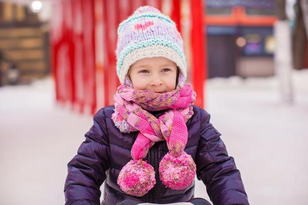 Adorável menina feliz patinando na pista de gelo