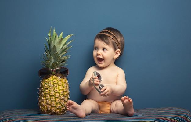 Adorável menina feliz sentada brincando com um abacaxi em um fundo azul