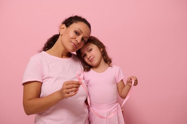 Adorável menina, inclina-se sobre o ombro da mãe, ambas vestidas com roupa de cor rosa, segura fitas de cetim rosa, sorriso fofo, olhando para a câmera. dia mundial da conscientização do câncer de mama. luta contra o câncer. copie o espaço