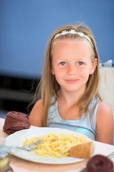 Adorável menina jantando no café ao ar livre
