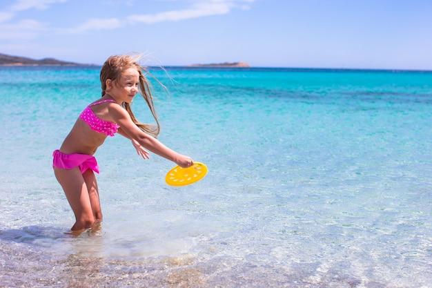 Adorável menina jogando frisbee durante férias tropicais