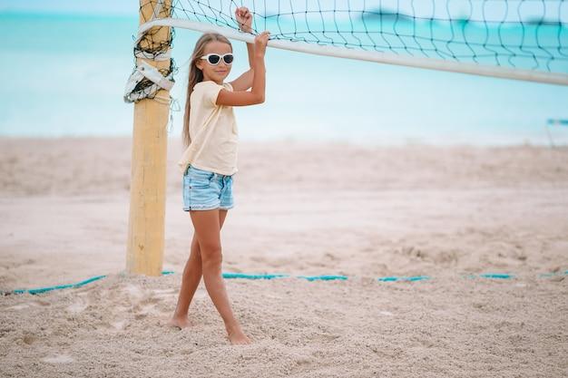 Adorável menina jogando vôlei na praia com bola.