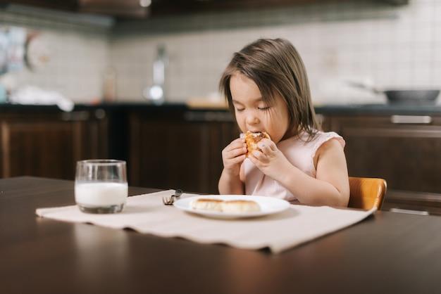 Adorável menina linda comendo bolo de queijo com as mãos no almoço