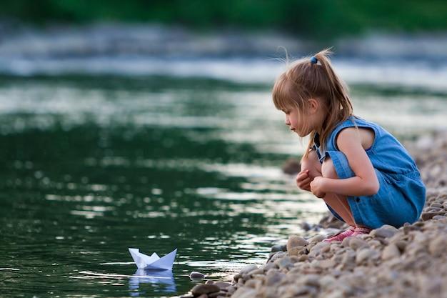 Adorável menina loira bonitinha no vestido azul em seixos da margem do rio, brincando com o barco de origami de papel branco na água azul cintilante bokeh
