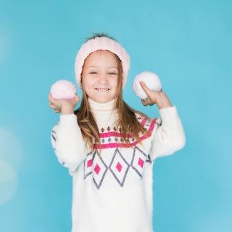 Adorável menina loira com bolas de neve
