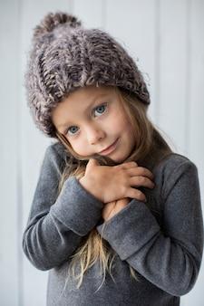 Adorável menina loira com chapéu de inverno
