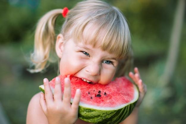 Adorável menina loira come uma fatia de melancia ao ar livre