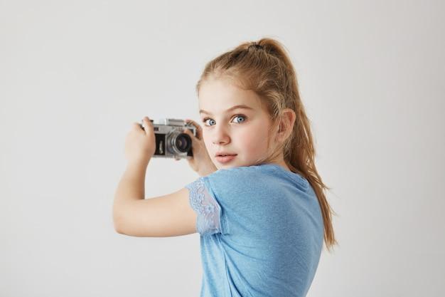Adorável menina loira pequena com olhos azuis, vai tirar selfie. ela olha para trás com expressão assustada quando ouve a mãe entrar no quarto