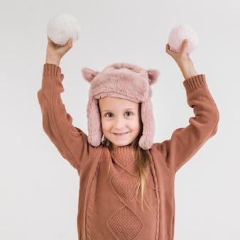 Adorável menina loira segurando bolas de neve