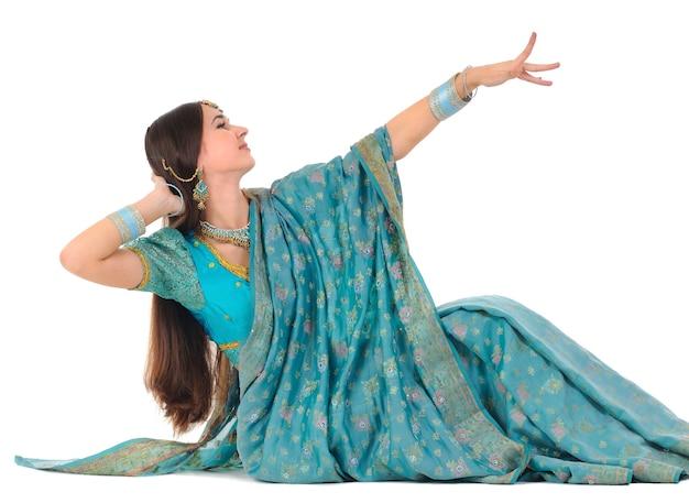 Adorável menina morena sentada com cabelo comprido em roupas tradicionais indianas azuis posando mostrando o movimento de dança nacional. isolado em fundo branco