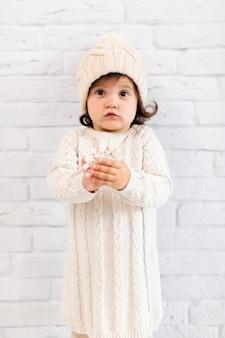 Adorável menina, mostrando um floco de neve