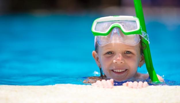 Adorável menina na máscara e óculos de proteção na piscina