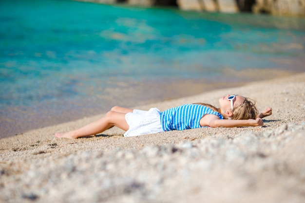 Adorável menina na praia durante as férias na europa