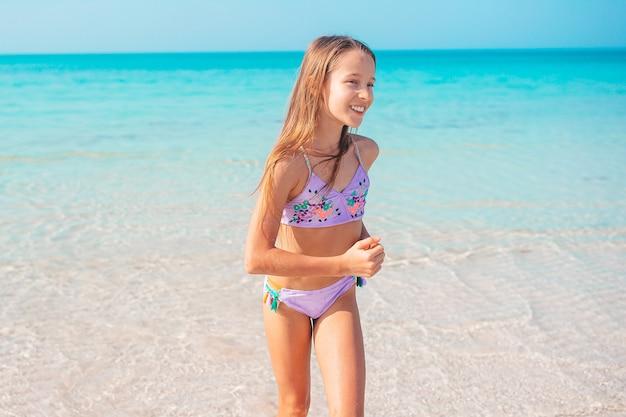 Adorável menina na praia nas férias de verão
