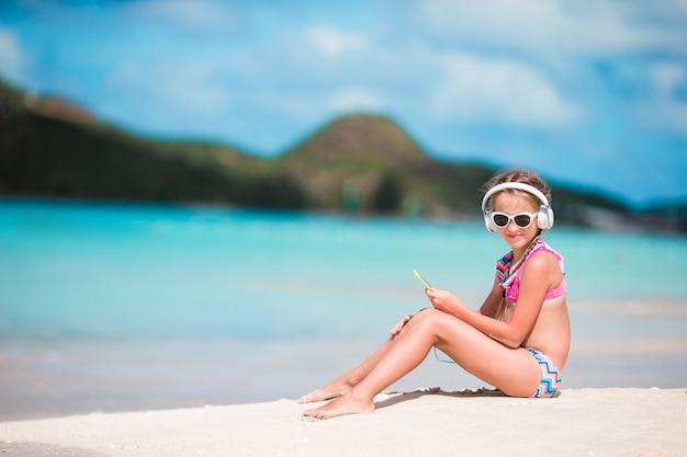 Adorável menina na praia ouvindo a música em grandes fones de ouvido