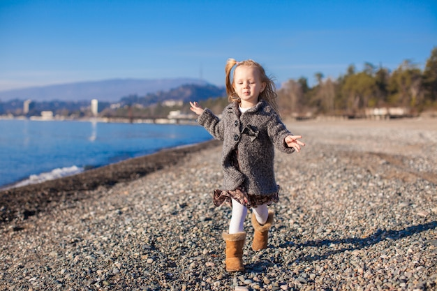 Adorável menina na praia se divertindo no dia quente de inverno