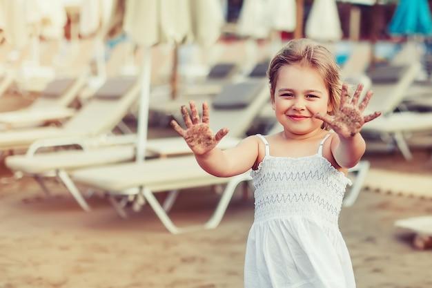 Adorável menina natural rosto natural casual retrato feminino estilo de vida beleza alegre menina na praia do mar jogar. conceito de infância