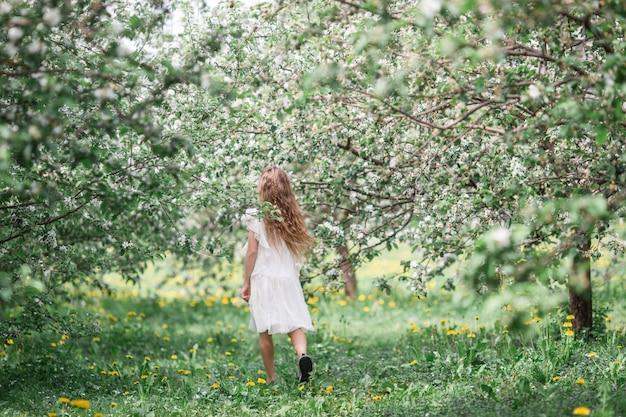 Adorável menina no jardim de apple florescendo em lindo dia de primavera
