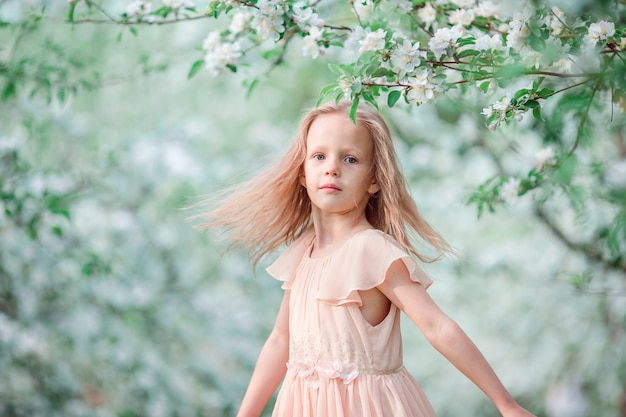 Adorável menina no jardim de cerejeira desabrocham na primavera