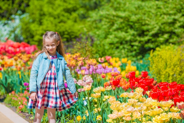 Adorável menina no jardim de tulipas florescendo