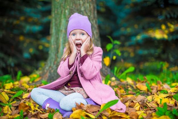 Adorável menina no outono park em dia ensolarado de outono