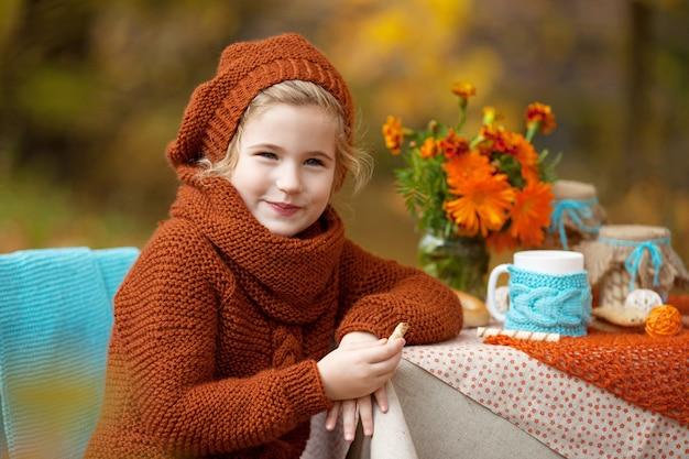 Adorável menina no piquenique no parque de outono. menina bonitinha tendo chá lá fora, no jardim de outono. feliz anos de infância. conceito sazonal.