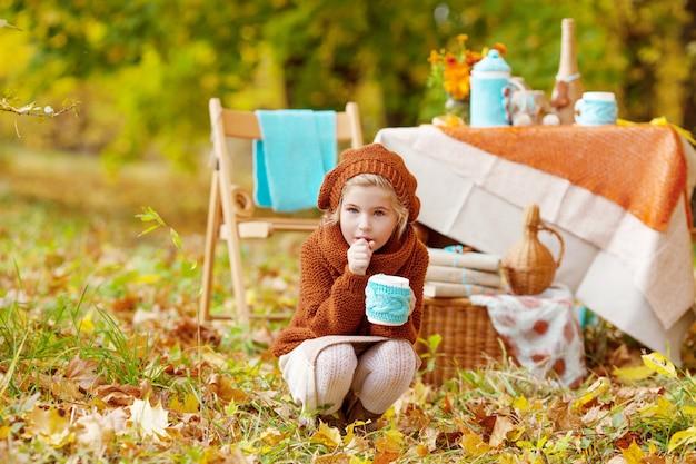 Adorável menina no piquenique no parque de outono. menina bonitinha tendo chá lá fora, no jardim de outono. menina bebendo chá. feliz anos de infância. conceito sazonal.