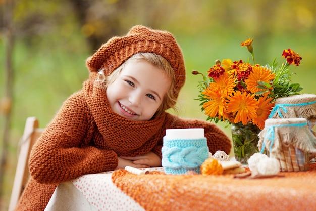 Adorável menina no piquenique no parque de outono. menina sorridente, tendo a festa do chá lá fora, no jardim de outono. feliz anos de infância. conceito sazonal.