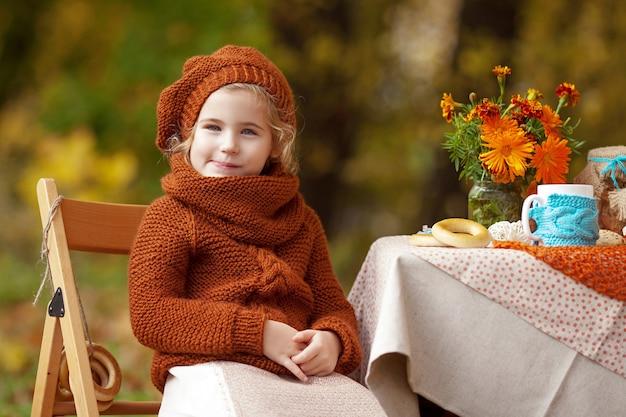 Adorável menina no piquenique no parque outono.