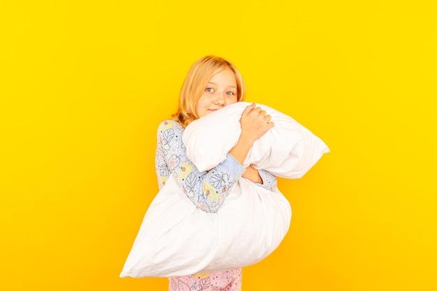 Adorável menina olhando para a câmera e abraçando um fundo de almofada de uma parede amarela.