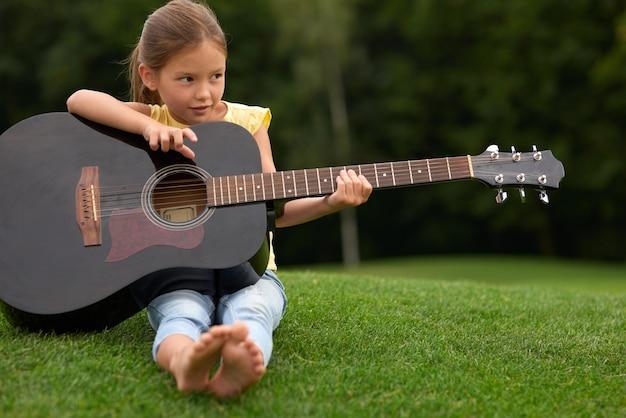 Adorável menina olhando para o lado e segurando um violão sentada em uma grama verde em um parque de gastos