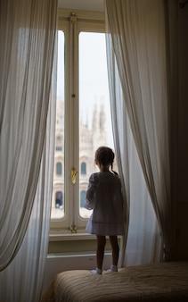 Adorável menina olhando pela janela no duomo, milão, itália