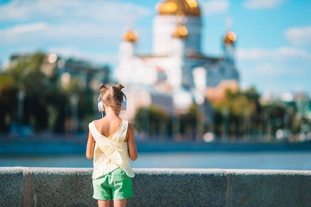 Adorável menina ouvindo música no parque