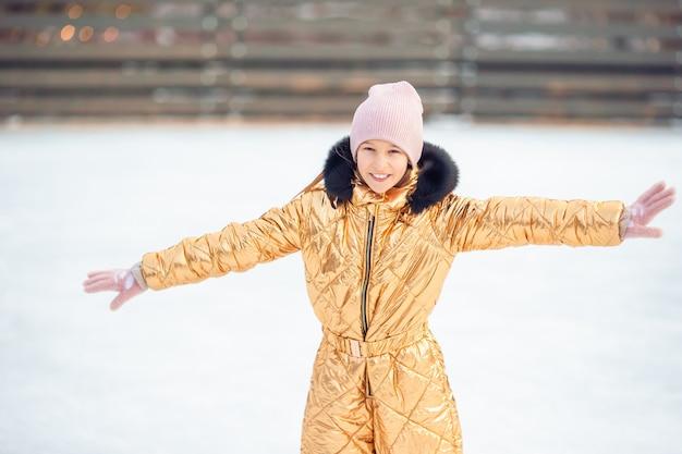 Adorável menina patinando na pista de gelo