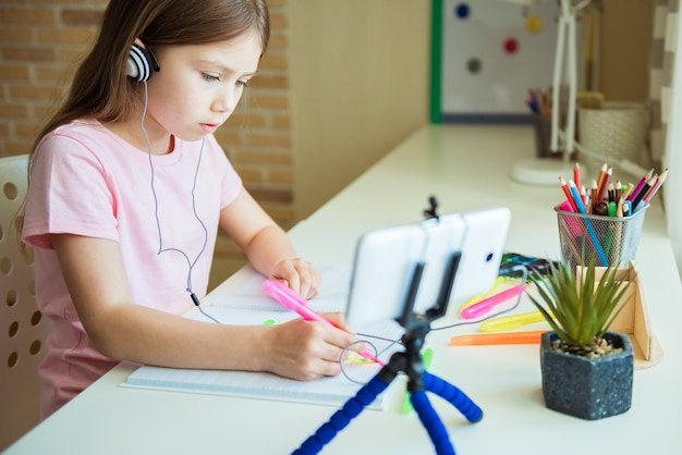 Adorável menina pintando com lápis de cor em casa, no jardim de infância ou na pré-escola. jogos criativos para crianças que ficam em casa