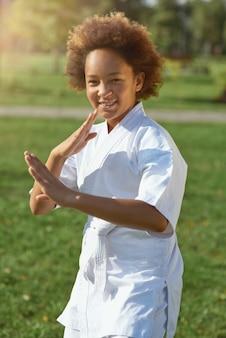 Adorável menina praticando artes marciais ao ar livre