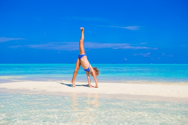 Adorável menina se divertindo fazendo cartwheel na praia de areia branca tropical