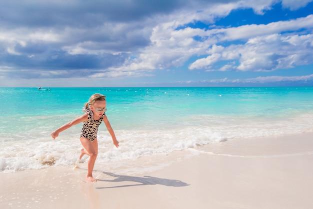 Adorável menina se divertir na água rasa durante as férias de verão