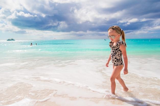 Adorável menina se divertir na água rasa na praia branca