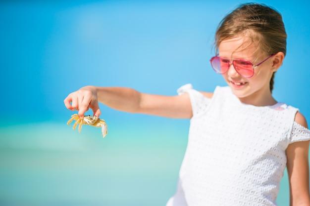 Adorável menina segurando caranguejo na praia